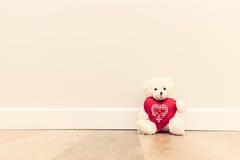 Urso de peluche bonito com coração vermelho grande do luxuoso Assento no assoalho de madeira contra a parede branca Imagem de Stock