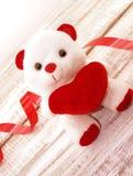 Urso de peluche branco que guarda um coração vermelho na parte traseira de madeira rústica branca Fotografia de Stock