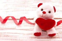 Urso de peluche branco que guarda um coração vermelho na parte traseira de madeira rústica branca Imagens de Stock