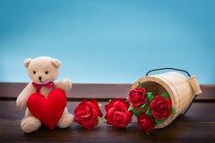 Urso de peluche com a decoração cor-de-rosa do coração na tabela de madeira sobre a parede Fotografia de Stock Royalty Free