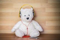 Urso de peluche com fones de ouvido e o telefone esperto no fundo de madeira Fotos de Stock Royalty Free