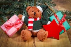 Urso de peluche com os presentes para o Natal, ramos spruce e a estrela vermelha Fotografia de Stock