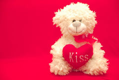 Urso de peluche com um coração em suas mãos em um fundo vermelho imagem de stock royalty free