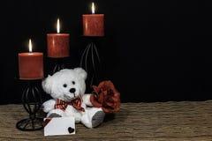 Urso de peluche de Cudlely com laço vermelho, a rosa vermelha, as velas vermelhas empoleiradas em castiçais pretos na esteira de  imagem de stock royalty free