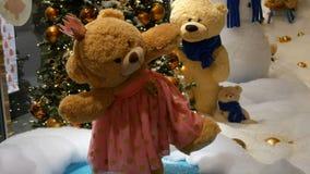 Urso de peluche do marrom do brinquedo da princesa em um vestido e em uma coroa que gerenciem ao redor em um shopping Natal-decor filme