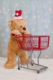 Urso de peluche do Natal que empurra o carro de compra imagens de stock royalty free