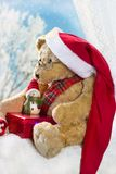 Urso de peluche do Natal que senta-se na janela no tempo de inverno Imagens de Stock Royalty Free