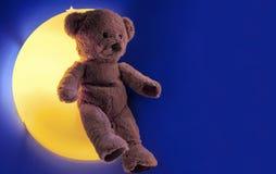 Urso de peluche em uma lâmpada amarela da noite em um fundo azul foto de stock royalty free