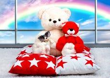 Urso de peluche macio que senta-se no descanso no fundo de Windows panorâmico Arco-íris Foto de Stock