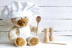 Urso de peluche no chapéu do cozinheiro chefe com fundo do alimento do sumário da colher Foto de Stock