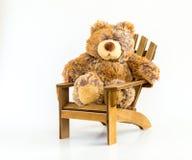 Urso de peluche peluches em uma cadeira de madeira marrom isolada no branco fotografia de stock royalty free