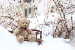 Urso de peluche que senta-se em um banco na neve Fotos de Stock Royalty Free