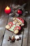 Urso do pão-de-espécie do Natal com o bulbo do Natal do galho do pinho nuts da estrela da canela da vela no assoalho de madeira Imagem de Stock