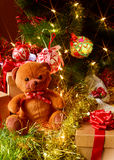 Urso e presentes de peluche sob uma árvore de Natal Imagem de Stock Royalty Free
