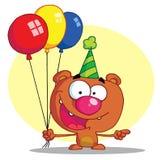 Urso feliz no chapéu do partido com balões Fotografia de Stock Royalty Free