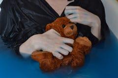Urso molhado pequeno de Brown nas mãos fotos de stock royalty free