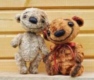 Ursos da peluche de encontro a uma parede de madeira Imagens de Stock Royalty Free