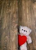 Ursos de peluche bonitos que guardam o coração vermelho com fundo de madeira velho Imagens de Stock Royalty Free