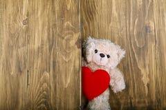Ursos de peluche bonitos que guardam o coração vermelho com fundo de madeira velho Fotografia de Stock Royalty Free