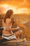 Ursprüngliche Frau, die einen Pfeil und Bogen hält Amazonas-Frau stockfotografie