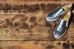 Ursprüngliche glänzende Schuhe in der Discoart liegen auf einer Weinleseholzoberfläche, die von gebratenen braunen Brettern gemac Lizenzfreie Stockfotos