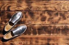 Ursprüngliche glänzende Schuhe in der Discoart liegen auf einer Weinleseholzoberfläche, die von gebratenen braunen Brettern gemac Stockfotografie
