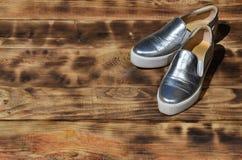 Ursprüngliche glänzende Schuhe in der Discoart liegen auf einer Weinleseholzoberfläche, die von gebratenen braunen Brettern gemac Lizenzfreie Stockfotografie