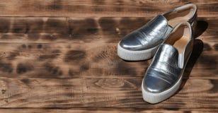 Ursprüngliche glänzende Schuhe in der Discoart liegen auf einer Weinleseholzoberfläche, die von gebratenen braunen Brettern gemac Stockbilder