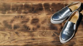 Ursprüngliche glänzende Schuhe in der Discoart liegen auf einer Weinleseholzoberfläche, die von gebratenen braunen Brettern gemac Lizenzfreies Stockbild
