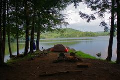 Ursprünglicher Bushcraft-Campingplatz mit einem Zelt, einem Stuhl, einem Stuhl und einem Lagerfeuer in der Adirondack-Gebirgswild Lizenzfreies Stockbild