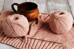 Ursprüngliches exklusives gestricktes Muster des empfindlichen rosa Garns und der schönen Lehmschale auf hellem hölzernem Hinterg lizenzfreies stockfoto