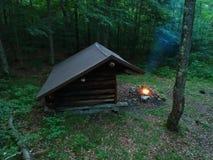 Ursprüngliches Mageres Bushcraft Adirondack zum Schutz mit Lagerfeuer in der Wildnis Lizenzfreies Stockfoto