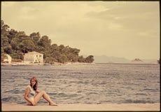 Ursprüngliches Weinlesefarbdia ab 1960 s, junge Frau, die vorbei sitzt Stockbilder