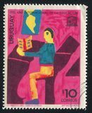 Children`s Drawing. URUGUAY - CIRCA 1970: stamp printed by Uruguay, shows Children`s Drawing, Boy Sitting at School Desk, circa 1970 Stock Image