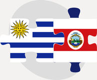 Uruguay and Costa Rica Flags in puzzle Royalty Free Stock Photo