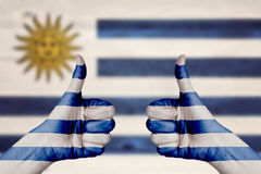 Uruguay flag painted on female hands thumbs up Stock Photography