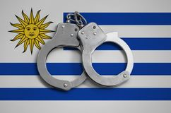 Uruguay flag and police handcuffs. The concept of observance of the law in the country and protection from crime royalty free stock photo