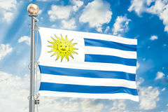Uruguay flag waving in blue cloudy sky, 3D rendering Stock Photos