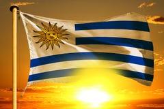 Uruguay flag weaving on the beautiful orange sunset with clouds background. Uruguay flag weaving on the beautiful orange sunset background stock photos