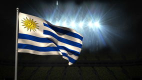 Uruguay national flag waving on flagpole. On black background with spotlights stock footage