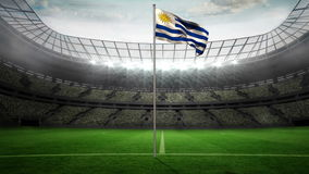 Uruguay national flag waving on flagpole. In football stadium with flashes stock video footage
