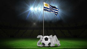 Uruguay national flag waving on flagpole with 2014 message. On football pitch with flashes stock footage