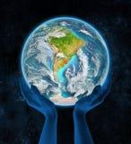 Uruguay op aarde in handen Stock Afbeelding