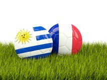 Uruguay vs France. Soccer concept. Footballs with flags on green Stock Photo
