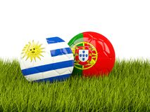 Uruguay vs Portugal. Soccer concept. Footballs with flags on gre Stock Photos