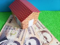 Uruguayan banknotes, figure of a house on green surface and blue background. Backdrop for mortgage and housing value ads, loan for home construction and stock photos