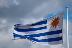 Uruguayan blauw en de witte vlag met gouden zon verzinnebeelden het klappen in wind met donkere wolken Royalty-vrije Stock Foto's
