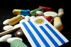 Uruguayan flag with lot of medical pills isolated on black backg Stock Photo