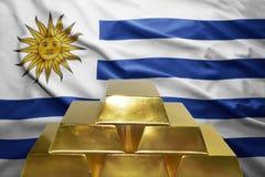 Uruguayan gold reserves. Shining golden bullions on the uruguayan flag background Stock Photography