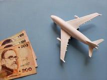 uruguayische Banknoten, weißes Plastikflugzeug und blauer Hintergrund stockfotos